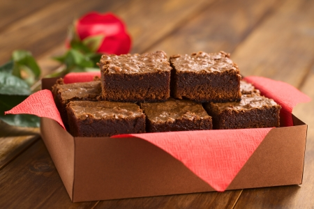 Freshly baked brownies in a brown paper box with red napkin, with red rose in the back (Selective Focus, Focus on the upper left brownie)