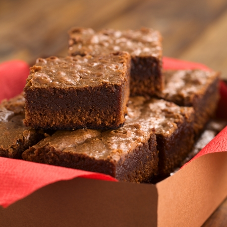 Freshly baked brownies in a brown paper box with red napkin (Selective Focus, Focus on the first brownie on the top) photo