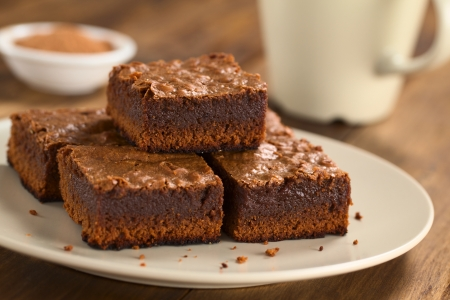 Freshly baked brownie pieces on a plate with cup in the back (Selective Focus, Focus on the left front part of the upper brownie) Stockfoto