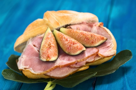 Fresh fig slices on smoked ham sandwich on fig leaves on blue wood (Selective Focus, Focus on the middle of the two fig slices on the left) photo