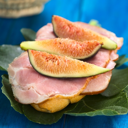 cold cuts: Fresh fig slices on smoked ham sandwich on fig leaves on blue wood (Selective Focus, Focus on the first fig slice)