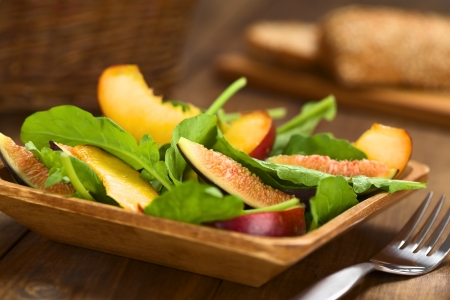 Fresh vegetarian salad made of fig, nectarine, spinach, cucumber and lettuce on wooden plate with wholewheat bread in the back (Selective Focus, Focus on the fig slice in the front)    photo