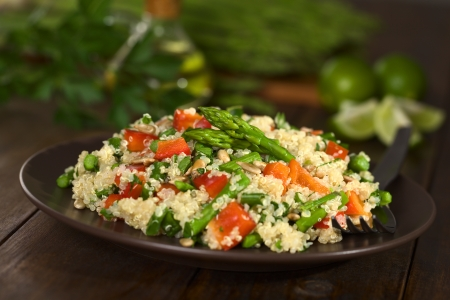 Vegetarian quinoa dish with green asparagus and red bell pepper, sprinkled with parsley and roasted sunflower seeds (Selective Focus, Focus on the asparagus heads on the dish)     Stockfoto
