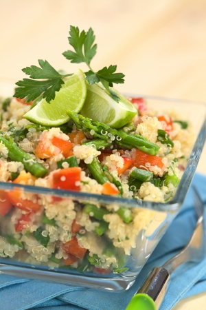 Vegetarian quinoa dish with green asparagus and red bell pepper, garnished with lime wedges and parsley leaf, served in glass bowl (Selective Focus, Focus on the asparagus head on the dish)