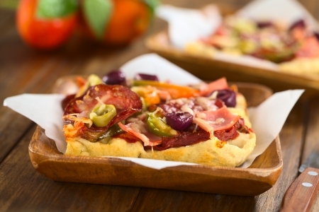 Fresh homemade pizza piece with tomato sauce, ham, salami, olives, bell pepper and cheese on top, served on sandwich paper on wooden plate (Selective Focus, Focus on the front of the olive slices) photo