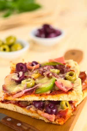 Fresh homemade pizza pieces with tomato sauce, ham, salami, olives, bell pepper and cheese on top on wooden board with knife (Selective Focus, Focus one third into the image) photo