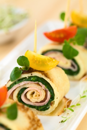 Crepe rolls as finger food filled with spinach and ham garnished with cherry tomato and watercress (Selective Focus, Focus on the right upper part of the crepe roll)
