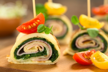 Crepe rolls as finger food filled with spinach and ham garnished with cherry tomato and watercress served on wooden board (Selective Focus, Focus on the upper part of the crepe roll)  photo