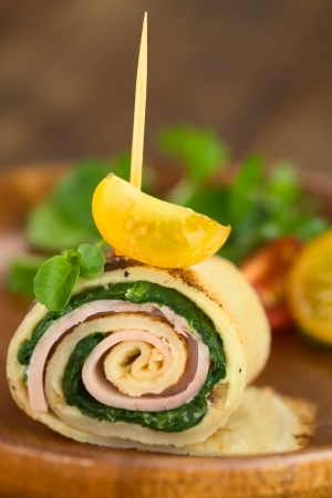 Crepe roll as finger food filled with spinach and ham garnished with cherry tomato and watercress served on wooden plate (Selective Focus, Focus on the upper part of the crepe roll and on the front of the cherry tomato on top)  photo