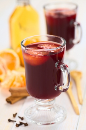 spiced: Hot spiced mulled red  wine with mandarin on top, with cloves, cinnamon sticks, mandarin, wooden spoon and a small bottle of rum (Selective Focus, Focus on the front of the rim and the handle of the glass)  Stock Photo
