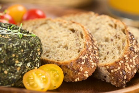 flaxseed: Slices of wholegrain bread with goat cheese covered with herbs and yellow cherry tomato (Selective Focus, Focus on the front of the bread slices)