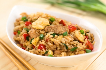 Homemade Chinese fried rice with vegetables, chicken and fried eggs served in bowl with chopsticks on the side (Selective Focus, Focus on the meat in the middle of the image) Stockfoto