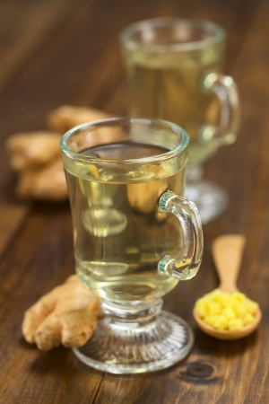 Freshly prepared hot ginger tea made of fresh ginger root served in glass (Selective Focus, Focus on the front of the rim and the handle of the glass) Stock Photo - 23790976