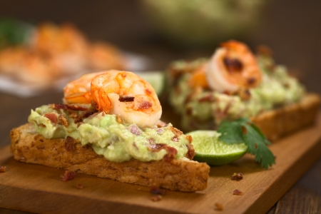 entree: Wholegrain toast bread slices with guacamole, fried shrimp and fried bacon pieces on wooden board (Selective Focus, Focus on the front of the shrimp on the first bread)