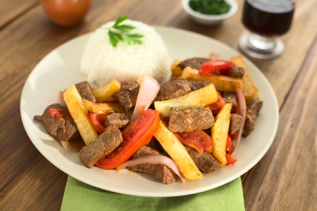 Peruaanse gerecht genaamd Lomo Saltado gemaakt van rundvlees, tomaat, rode ui en frietjes, geserveerd met rijst (selectieve aandacht, Focus een derde in de schaal)