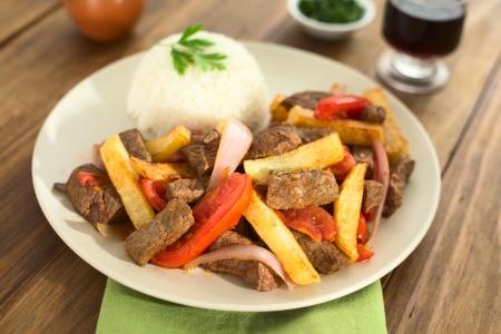 Plat péruvien appelé Lomo Saltado fait de viande de b?uf, tomate, oignon rouge et frites, servi avec du riz (sélective Focus, Focus tiers dans le plat)