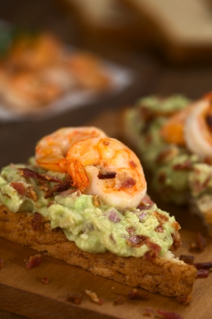 Wholegrain toast bread slices with guacamole, fried shrimp and fried bacon pieces on wooden board (Selective Focus, Focus on the front of the shrimp on the bread)  photo