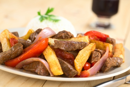 Peruvian dish called Lomo Saltado made of beef, tomato, red onion and French fries, served with rice (Selective Focus, Focus on the horizontal beef piece in the middle of the image)