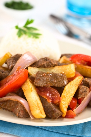 Peruvian dish called Lomo Saltado made of beef, tomato, red onion and French fries, served with rice (Selective Focus, Focus one third into the dish) Stock Photo