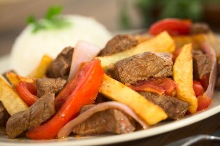 쇠고기, 토마토, 붉은 양파, 감자 튀김으로 만든 로모 Saltado라는 페루 요리는, (선택적 초점, 접시에 삼분의 초점) 쌀과 봉사