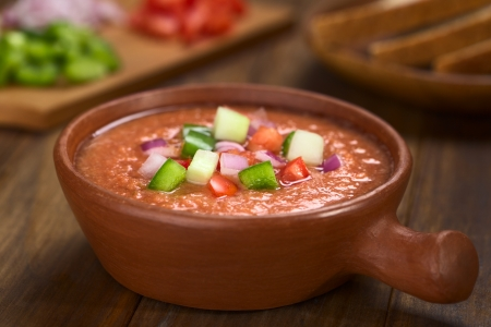 andalusian cuisine: Traditional Spanish cold vegetable soup made of tomato, cucumber, bell pepper, onion, garlic and olive oil served in rustic bowl (Selective Focus, Focus on the front of the vegetables on the top of the soup)
