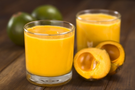 Milkshake made of the Peruvian fruit called lucuma  served in glass with lucuma fruits around  photo