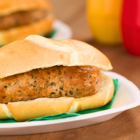bratwurst: Fried bratwurst in bun, traditional German fast food served on disposable plate with napkin, ketchup and mustard in the back  Stock Photo