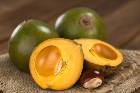 Peruvian fruit called Lucuma (lat. Pouteria lucuma) which has a dry, sweet flesh, and is mostly used to prepare juices, milkshakes, yogurts, ice cream and other desserts (Selective Focus, Focus on the standing lucuma half)  Stockfoto