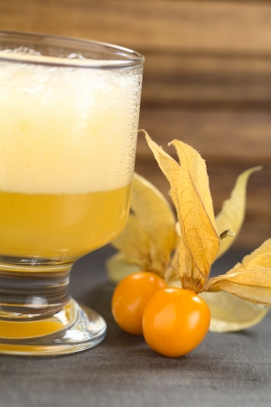 Physalis berries (lat. Physalis peruviana) with a Peruvian cocktail called Aguaymanto Sour (Physalis Sour) prepared from physalis juice, pisco (Peruvian grape hard liquor), syrup and egg white on the side (Selective Focus, Focus on the front of the first  photo