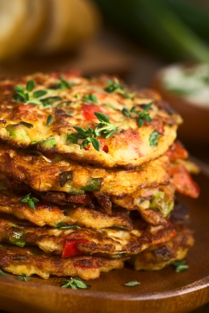 scallion: Vegetable and egg fritter made of zucchini, red bell pepper, eggs, green onions and thyme piled on a wooden plate with baguette slices and yogurt dip in the back (Selective Focus, Focus on the front of the thyme sprig on the top of the fritters and on the