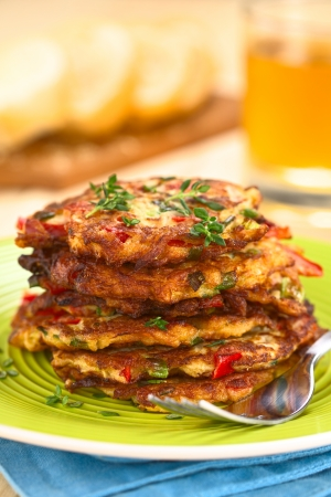 fritter: Vegetable and egg fritter made of zucchini, red bell pepper, eggs, green onions and thyme piled on a green plate with fork on the side (Selective Focus, Focus on the front of the thyme sprig on the top of the fritters and on the front of the top fritters) Stock Photo