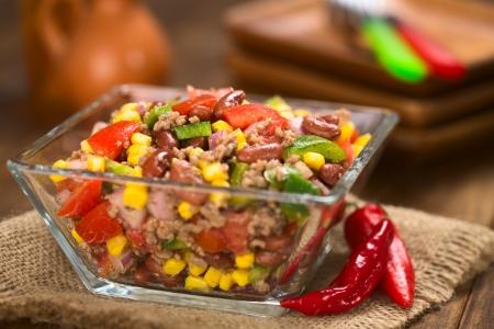 Chili con carne salade gemaakt van gehakt, bruine bonen, groene paprika, tomaat, mais en rode uien geserveerd in glazen kom (Selective Focus, Focus in het midden van de salade)