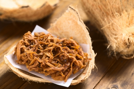 grated: Peruvian cocada, a traditional coconut dessert sold usually on the streets, made of grated coconut and brown sugar, which gives the dark color of the sweet (Selective Focus, Focus one third ino the cocada)