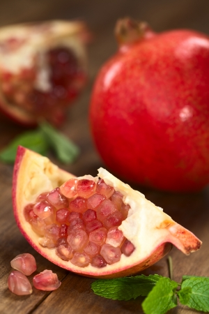 Open pomegranate fruit (lat. Punica granatum) with seeds (Selective Focus, Focus on the upper seeds) photo