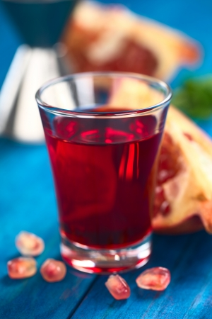 grenadine: Grenadine syrup in shot glass with pomegranate seeds in the front and pomegranate in the back (Selective Focus, Focus on the front rim of the glass) Stock Photo