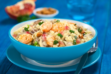 Couscous dish with shrimps, mushroom, almond, pomegranate seeds and green onion served in blue bowl with fork on the side (Selective Focus, Focus on the tails of the shrimps on the top of the meal)  photo