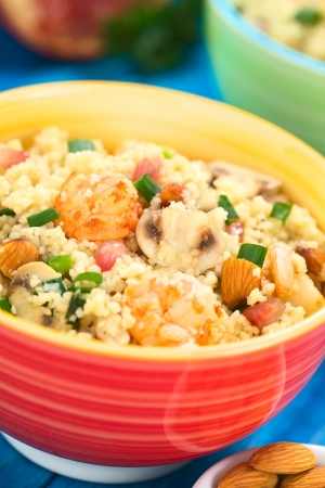 Couscous dish with shrimps, mushroom, almond, pomegranate seeds and green onion served in colorful bowl (Selective Focus, Focus on the tail of the shrimp on the top of the meal and on the mushroom slice next to it)  photo