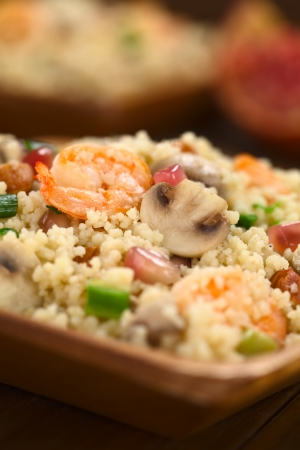 Couscous dish with shrimps, mushroom, almond, pomegranate seeds and green onion served on wooden plate (Selective Focus, Focus on the tail of the shrimp on the top of the meal and on the upper part of the mushroom slice next to it)  photo