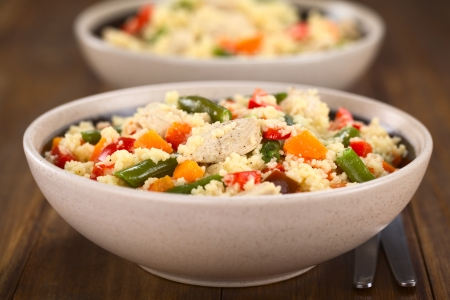 couscous: Two bowls of couscous dish with chicken, green bean, carrot and red bell pepper (Selective Focus, Focus on the chicken meat in the middle of the image)