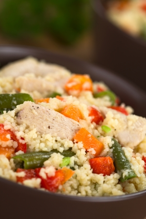 couscous: Couscous dish with chicken, green bean, carrot and red bell pepper served in a bowl (Selective Focus, Focus one third into the dish)