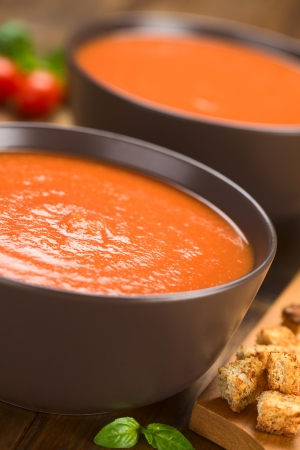 croutons: Fresh homemade tomato soup in brown bowls on dark wood with wholegrain croutons on the side (Selective Focus, Focus one third into the soup)