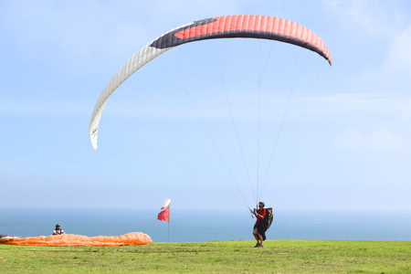 miraflores: LIMA, PERU - FEBRUARY 20, 2012  Unidentified person with a paraglider on the coast of Miraflores on February 20, 2012 in Lima, Peru  Paragliding is a popular sport on the coast of Miraflores, where winds are usually good and in good weather a big part of
