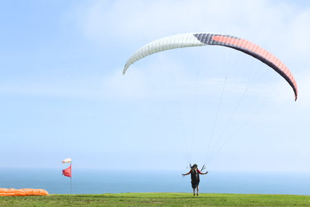 LIMA, PERU - FEBRUARY 20, 2012  Unidentified person taking off with a paraglider on the coast of Miraflores on February 20, 2012 in Lima, Peru  Paragliding is a popular sport on the coast of Miraflores, where winds are usually good and in good weather a b