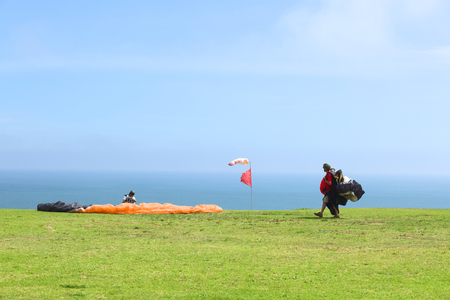 LIMA, PERU - FEBRUARY 20, 2012  Unidentified people with paragliders on the coast of Miraflores on February 20, 2012 in Lima, Peru  Paragliding is a popular sport on the coast of Miraflores, where winds are usually good and in good weather a big part of t