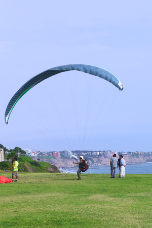 miraflores: LIMA, PERU - MARCH 19, 2012  Unidentified person with a paraglider on the coast of Miraflores with a view of the coast of Miraflores and Barranco in the back on March 19, 2012 in Lima, Peru  Paragliding is a popular sport on the coast of Miraflores, where