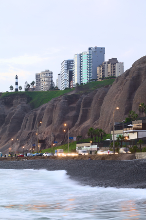 LIMA, PERU - APRIL 2, 2012  The steep coast and the lighthouse of the district of Miraflores as seen from the waterside in the evening on April 2, 2012 in Lima, Peru  Miraflores is a modern and upscale district, which attracts many tourists  Editorial
