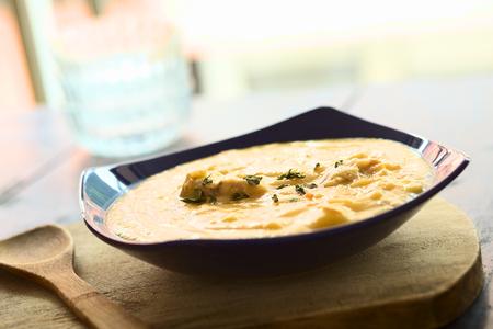 厚い黄スプリットピー スープ鶏といくつかのオレガノの葉を浮かべる木製基板 (選択的なフォーカス スープに 3 分の 1) のブルー スープ皿で提供し