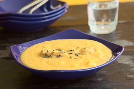 厚い黄スプリットピー スープ鶏といくつかのオレガノの葉を浮かべるブルー スープ プレート (選択的なフォーカス スープに 3 分の 1) で提供してい