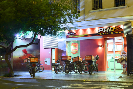 LIMA, PERU - MARCH 12, 2012: PHD Pizza Hut Delivery with many motorbikes in front on the Jose Larco Avenue in the district of Miraflores on March 12, 2012 in Lima, Peru.