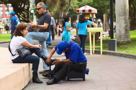 LIMA, PERU - MARCH 21, 2012: Unidentified man cleaning the shoes of an unidentified woman in Kennedy Park in the district of Miraflores on March 21, 2012 in Lima, Peru. Many people use the service of mobile shoe cleaners in Lima.